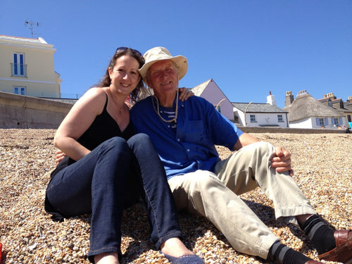 Tara Barton on Slapton Sands shingle beach in the sun with father Tony Barton