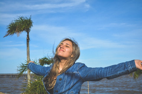 blond woman wearing blue shirt looking up to the blue sky with arms open and palm tree in background