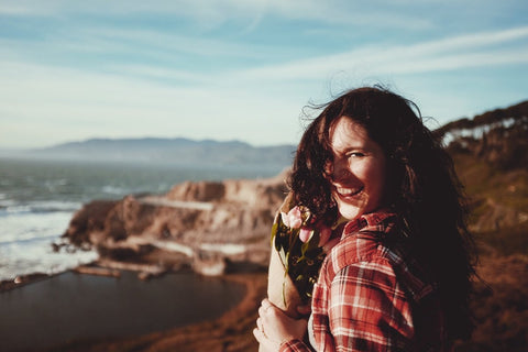 Beautiful cliff and coastline with brunette woman smiling and holding flowers looking back at camera