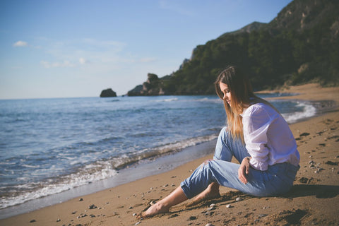 Thoughtful brunette woman sitting on beach with legs outstretched looking at the calm blue sea