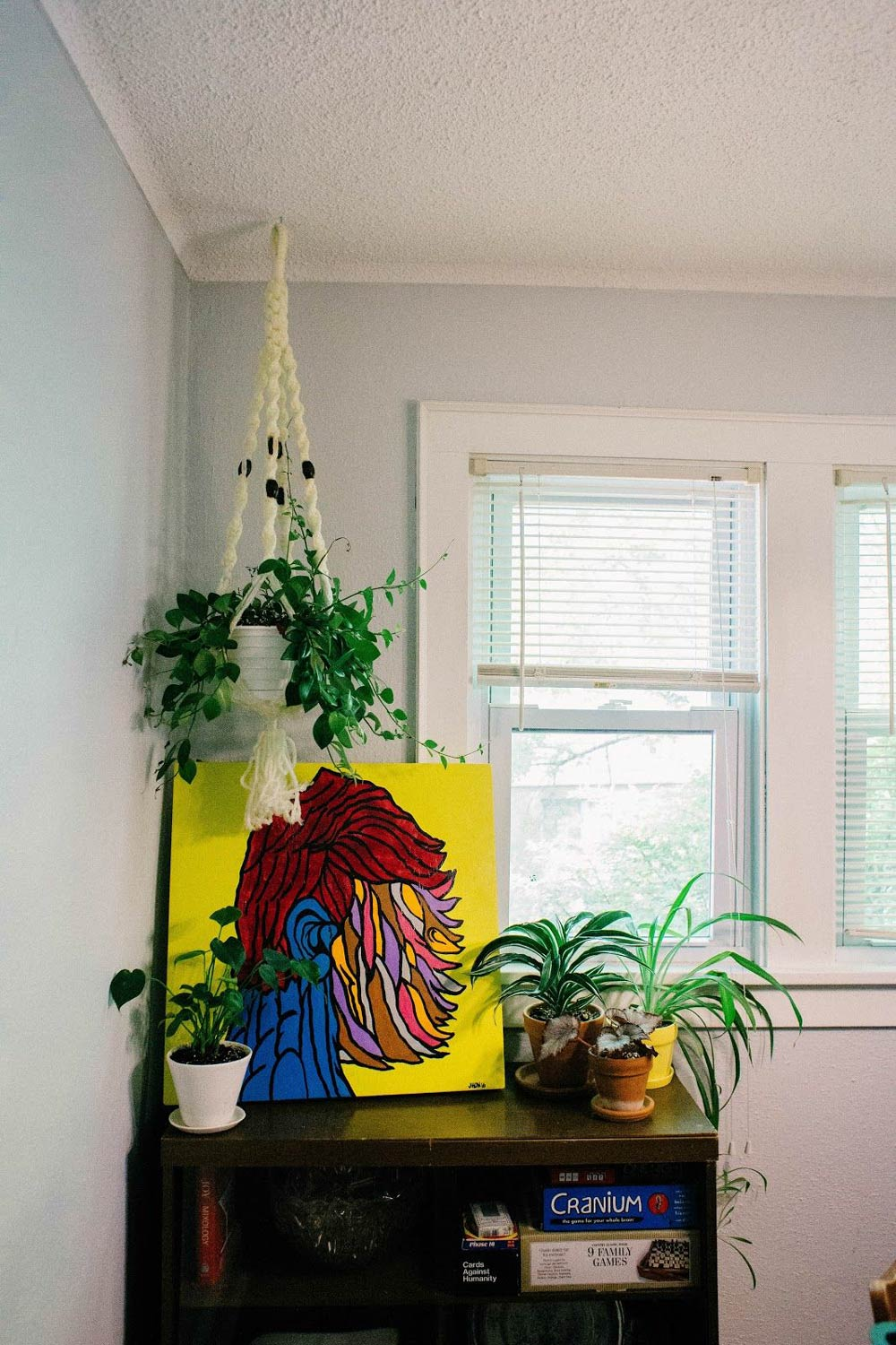 Hanging plant near dresser with art