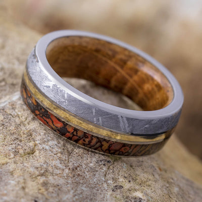Meteorite Ring With Oak Wood Inside pictured on rock
