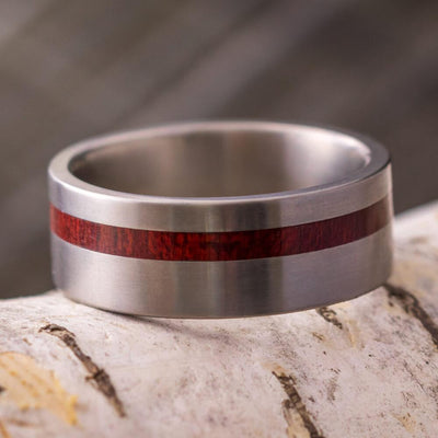 Titanium Wedding Band with Red Wood Pictured on Birch Bark