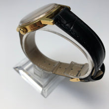 Gold watch on stand with black leather strap