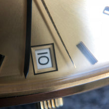Gold watch face date window macro