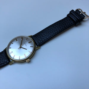 Gold watch with white face and black strap