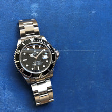 Submariner watch on blue book