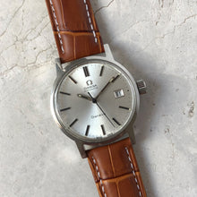 Omega watch with brown strap on tile