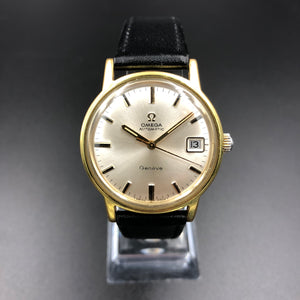 Vintage Omega watch with white face on black background
