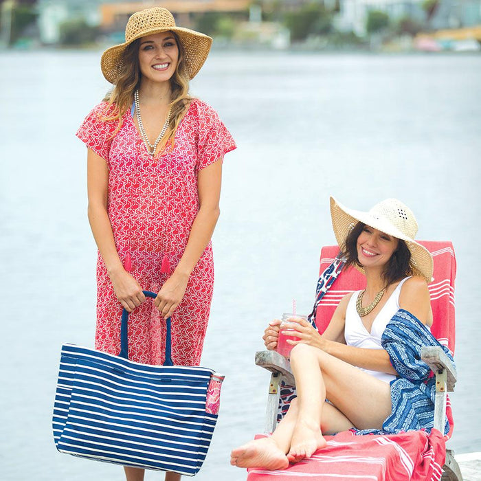 2 women in summery clothing - a red beach dress and blue tote bag, and a blue kimono