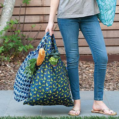 woman in jeans carrying 2 blu bags which are reusable shopping bags with stylish prints and designs