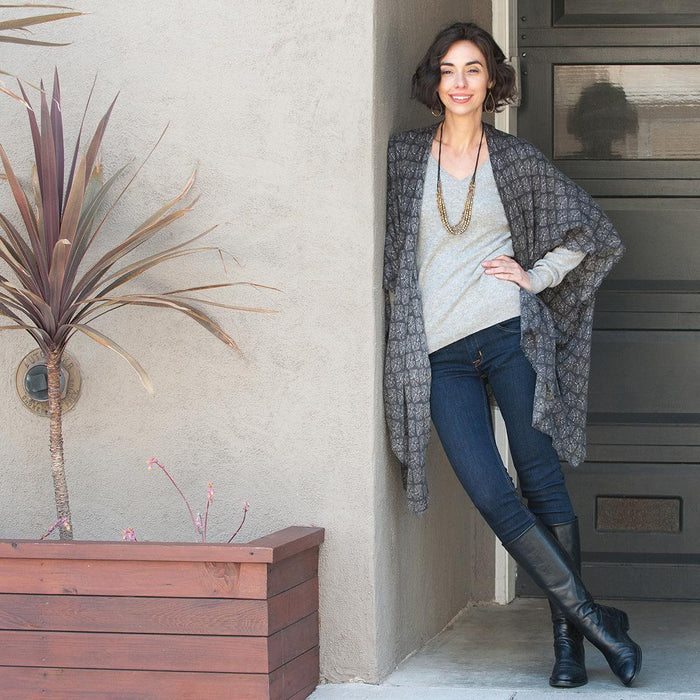 woman wearing a grey printed kimono cardigan with jeans and black boots