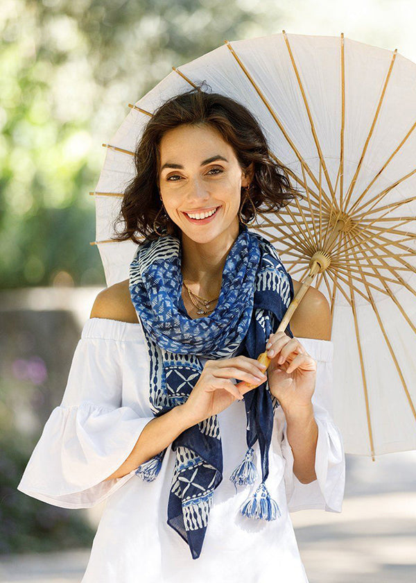 woman wearing a blue scarf and holding an umbrella