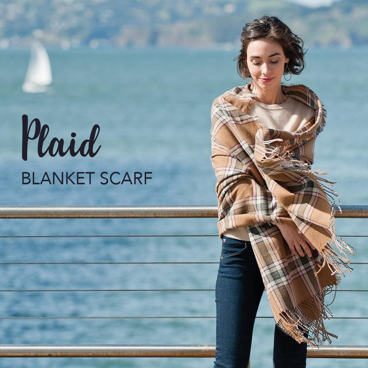 woman wearing a tan plaid blanket scarf by the bay