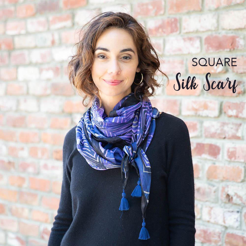 woman wearing a purple and blue printed silk square scarf in front of a brick wall
