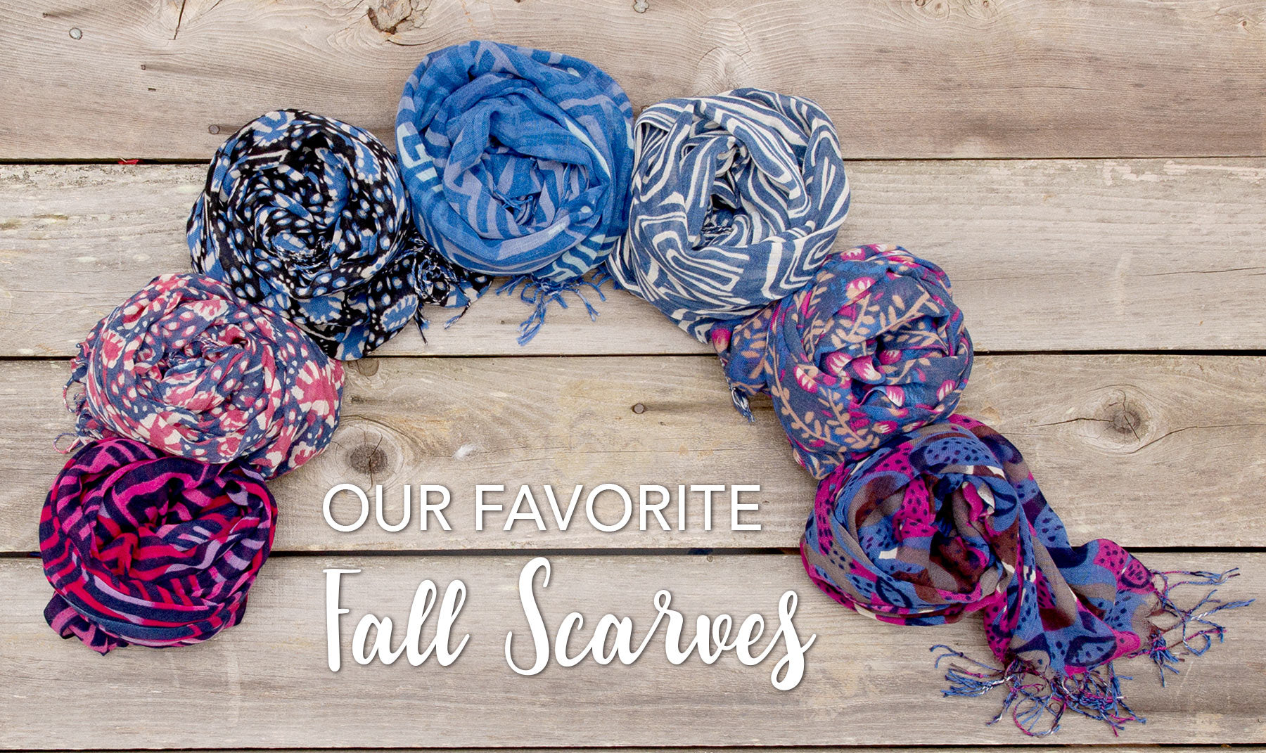 Flat lay on wood panels of coiled, colorful, fall scarves in blues and berries