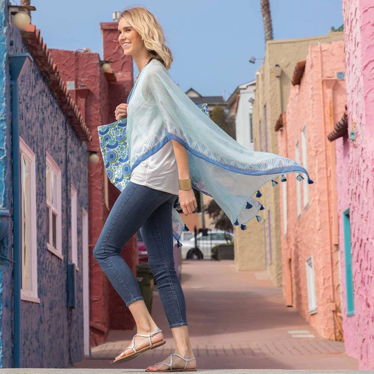 Woman wearing light blue kimono wrap in colorful Capitola, California