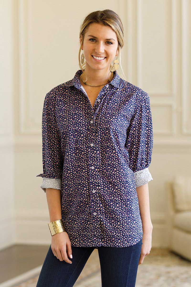 Woman wearing navy blue floral print button down shirt with dark jeans