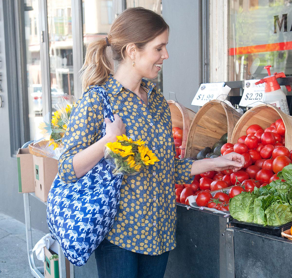 woman grocery shopping at a vegetable stand with a reusable blu bag