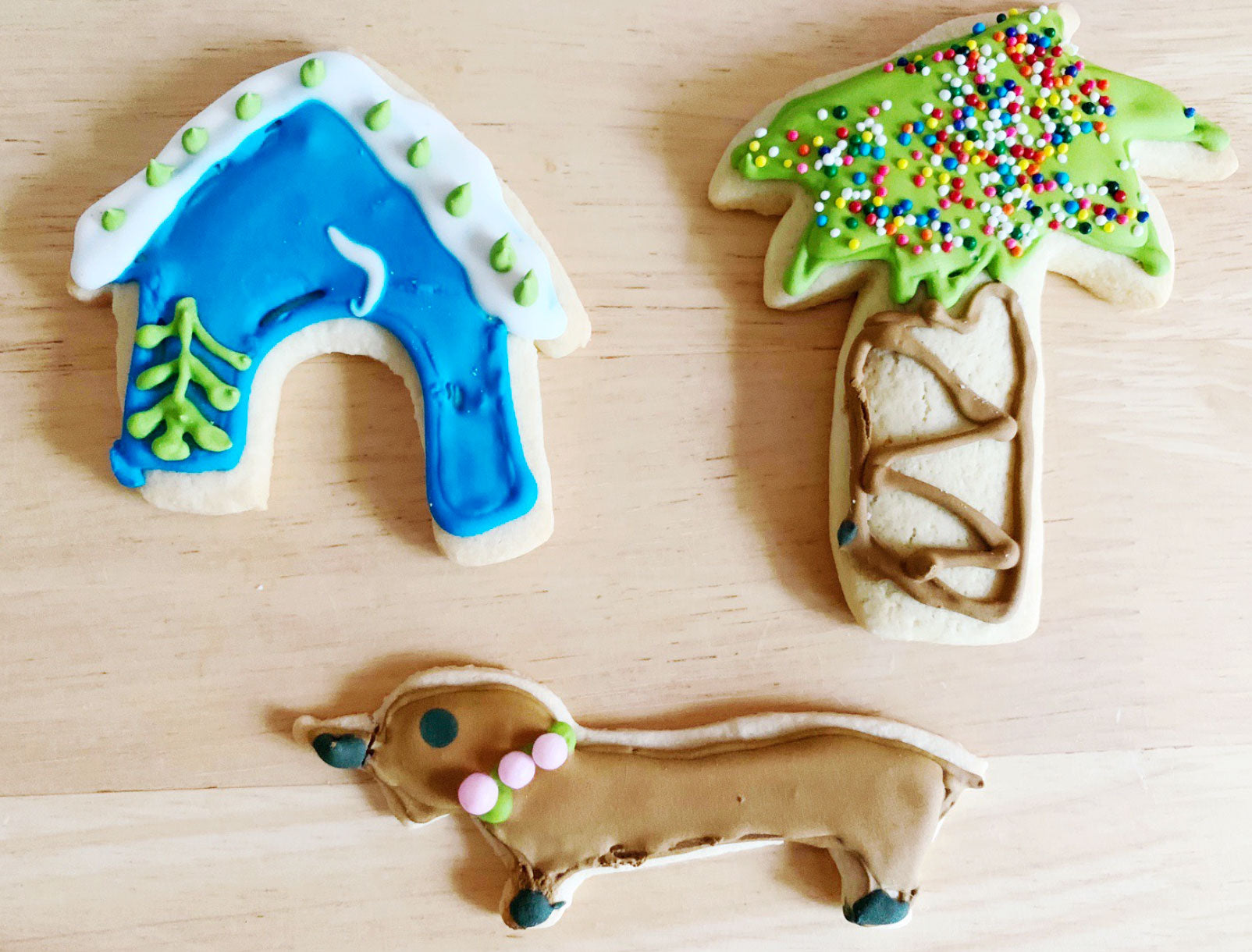 sugar cookies in the shape of a house, palm tree, and dachshund