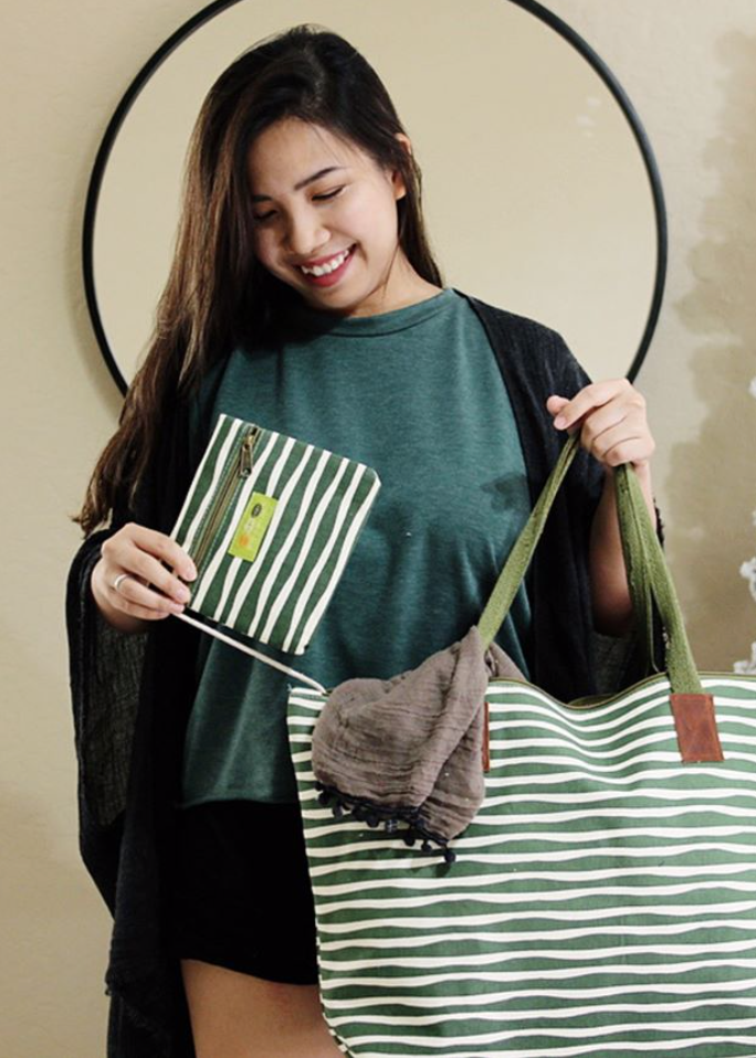 woman wearing green tshirt with black fringe kimono holding a green and white striped tote bag