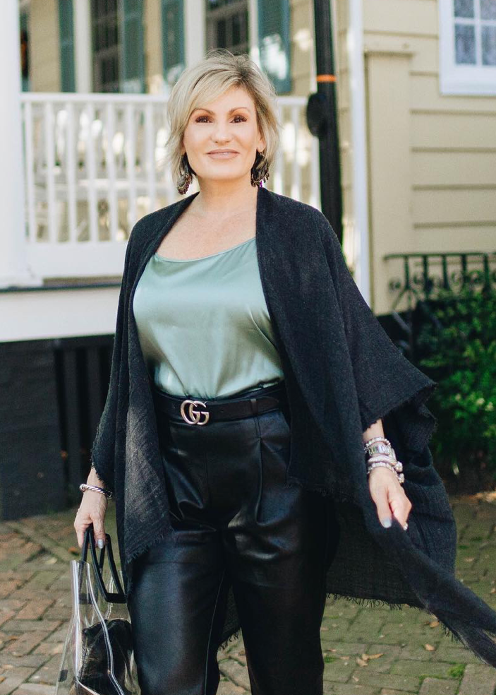 woman in front of a house wearing a black fringe kimono and black leather pants for an elegant evening out