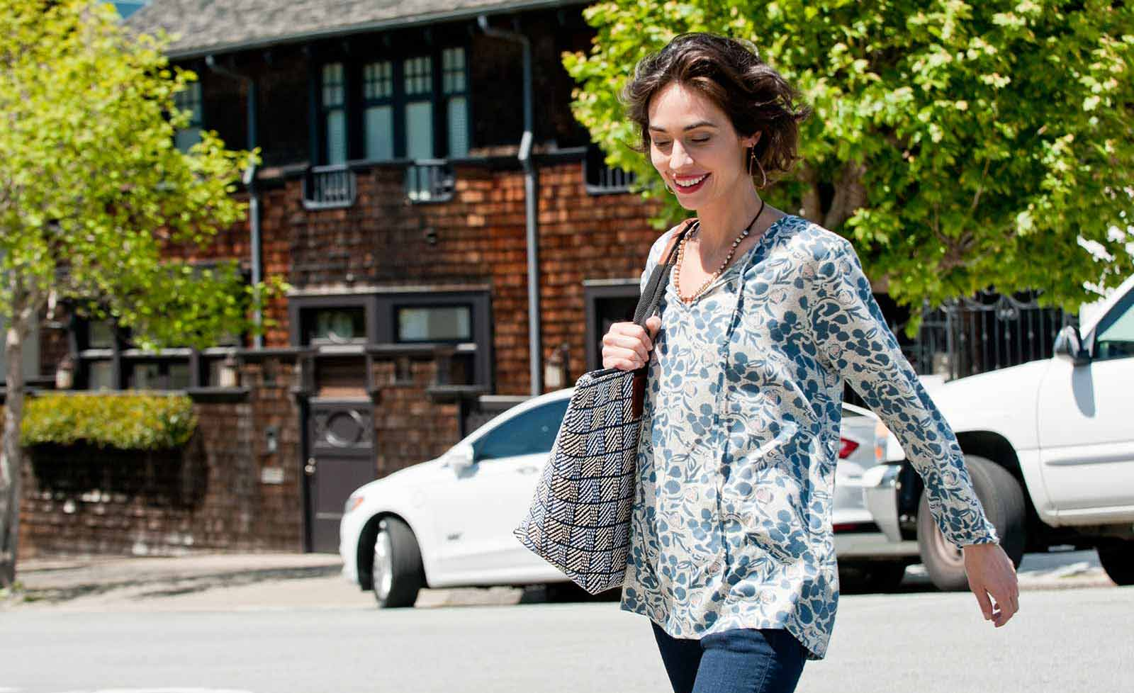 woman wearing white and blue peasant shirt and walking across the street