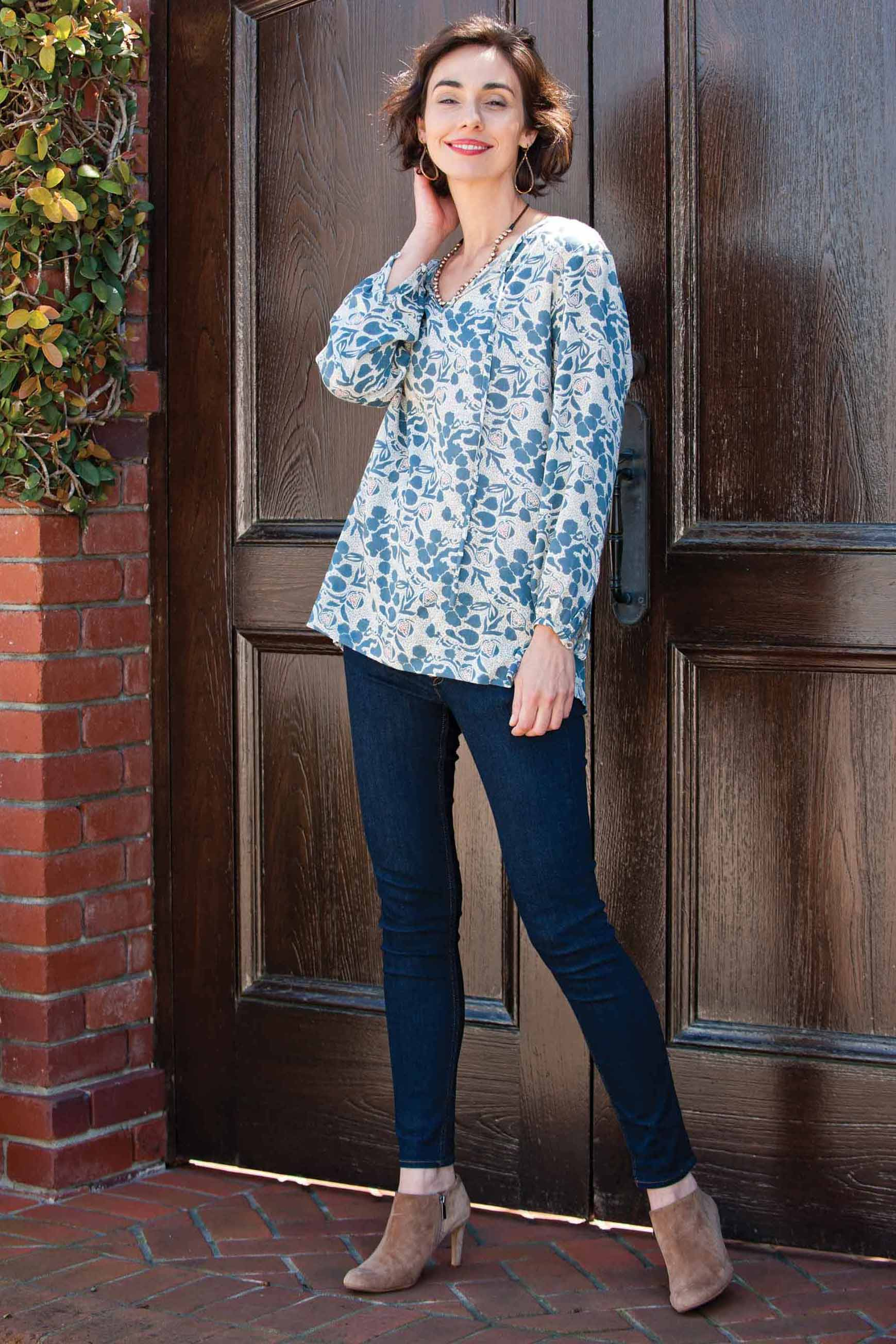 woman wearing white and blue peasant top with floral print