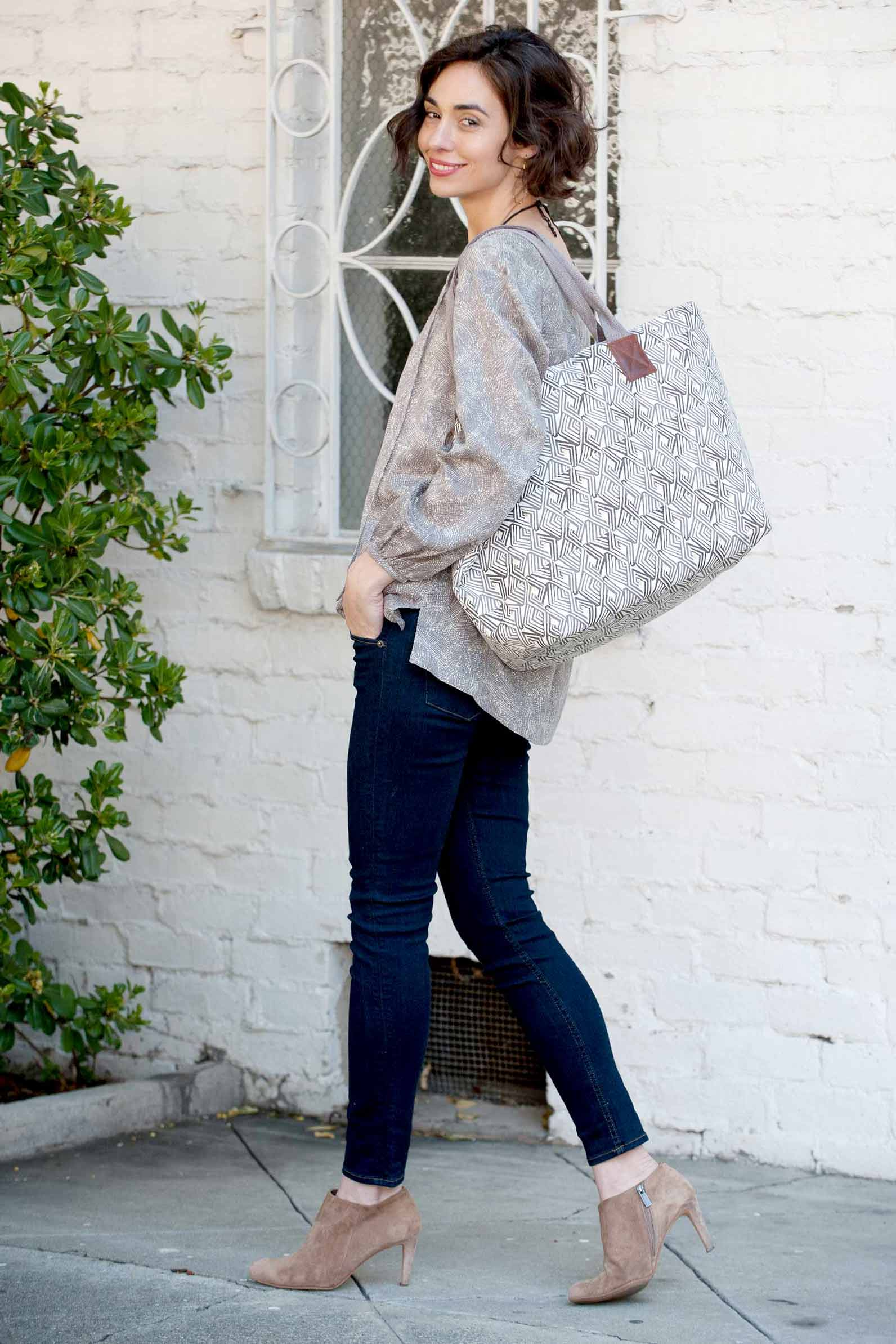 woman wearing grey tunic and grey tote bag with jeans