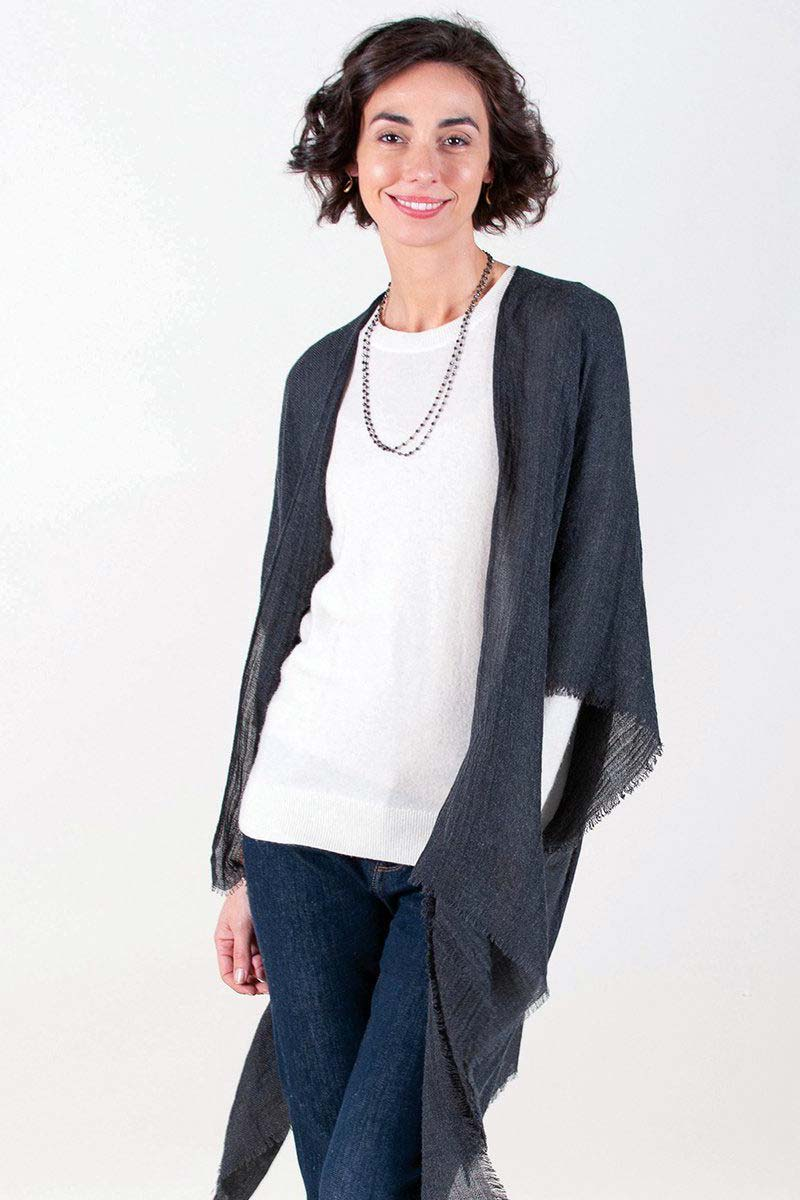 woman wearing black fringe kimono over sweater and jeans