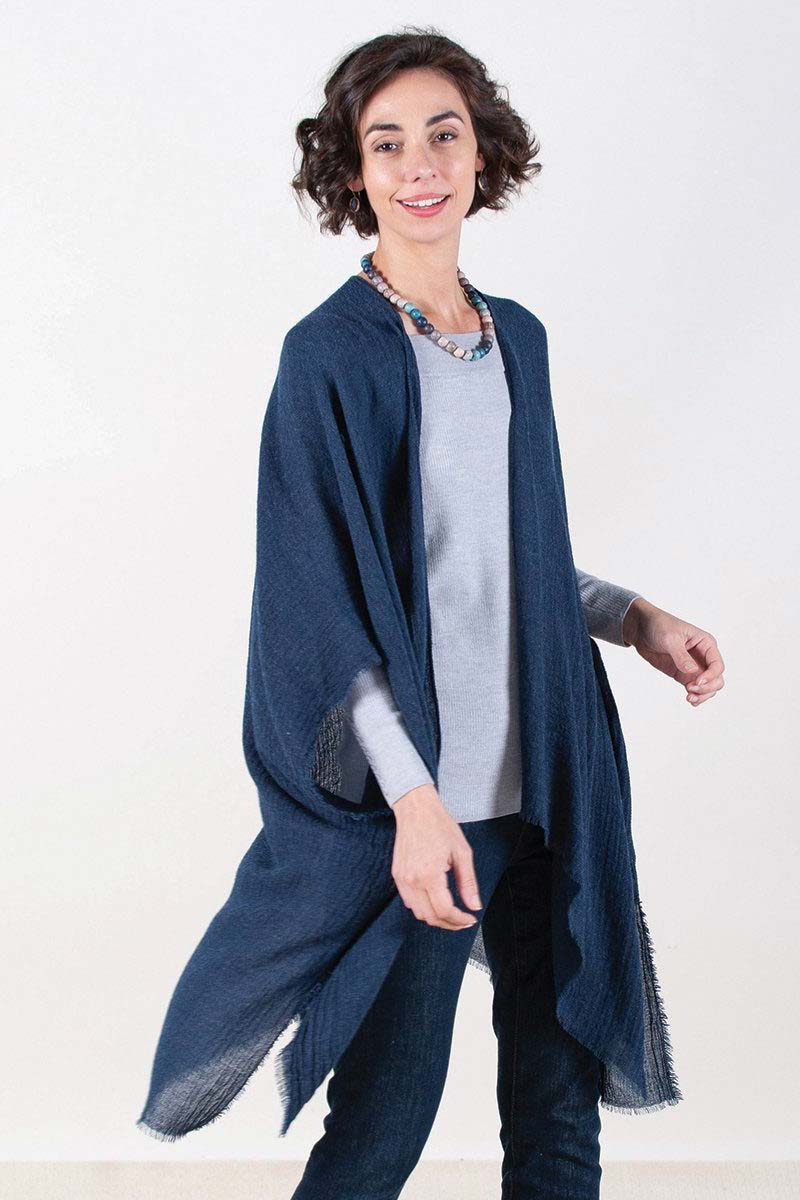 woman wearing blue fringe kimono over sweater and jeans