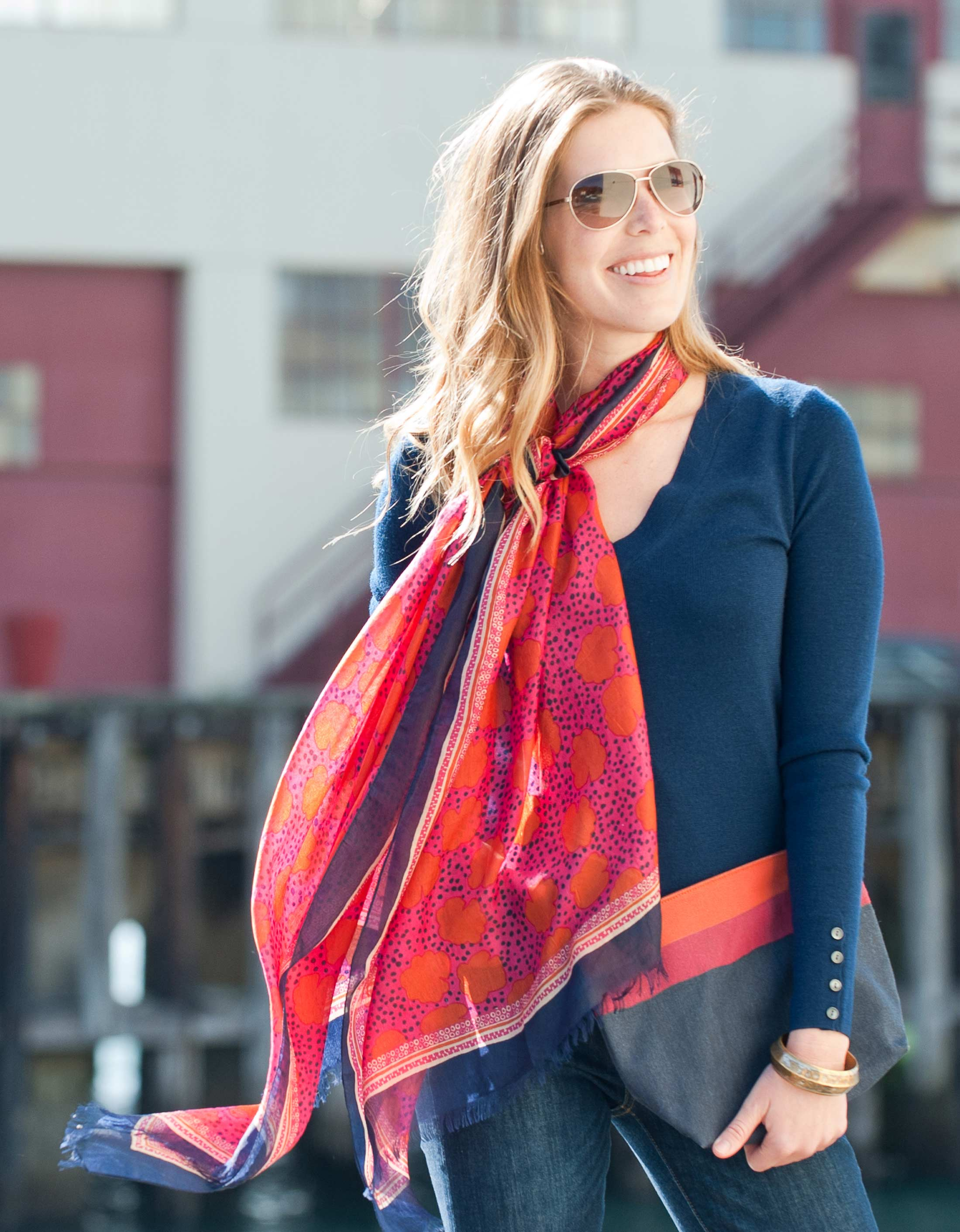 woman wearing navy sweater and red floral print silk scarf