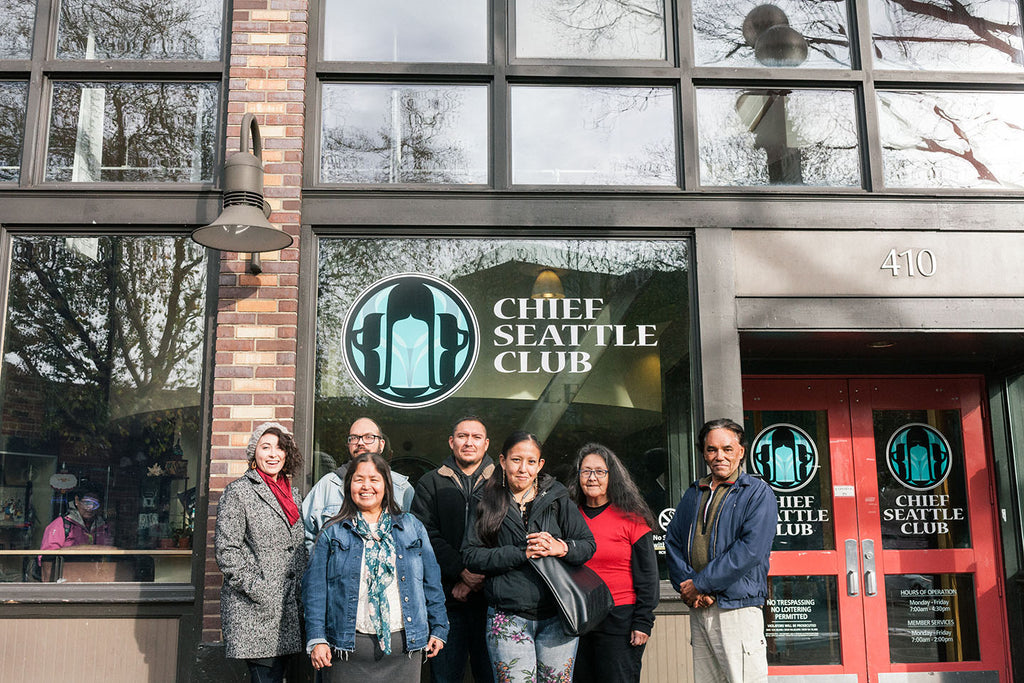 Chief Seattle Club's social enterprise, Native Works, stands in front of a the building and poses for a photo.