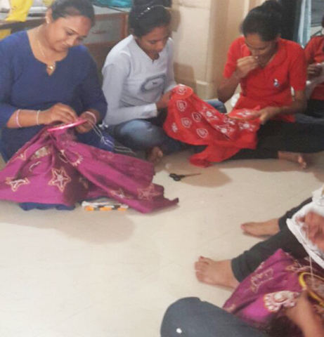 Women hand embroidering Christmas decorations in India