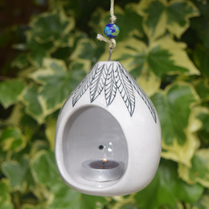 Featured in a garden- a black leaf pattern on a white tealight holder, also includes a blue bead on string.