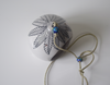 Top view- a black leaf pattern on a white tealight holder, also includes 2 blue beads on string.