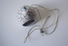 top view- black and white floral patterned tealight holder with blue beads on string
