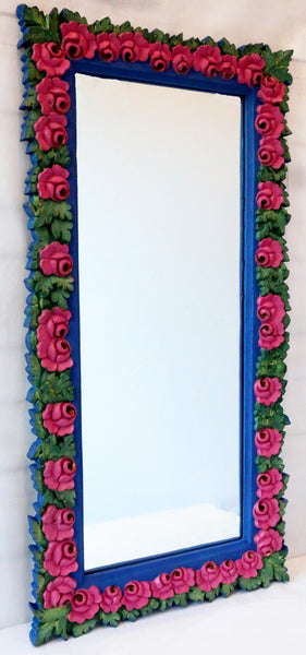 side view of indigo mirror with pink roses all around and green leaves.