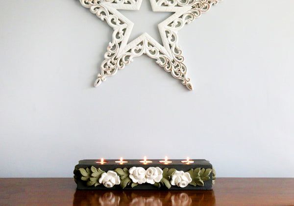 Charcoal tealight base with white roses and green leaves against a grey background with a white star