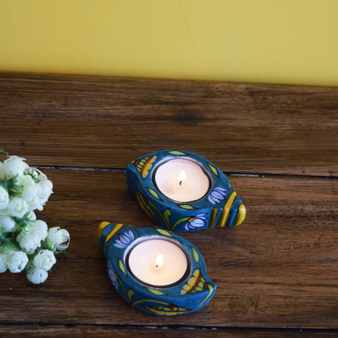 blue conch-shaped tealight holders painted in yellow and brown floral patterns