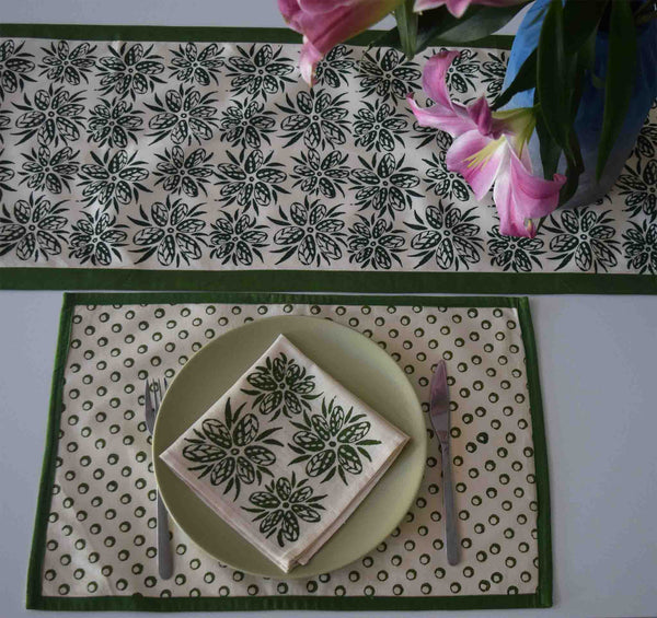 Cream with green floral pattern runner, geometric circles table mat and floral pattern napkin on a green plate in a table setting.