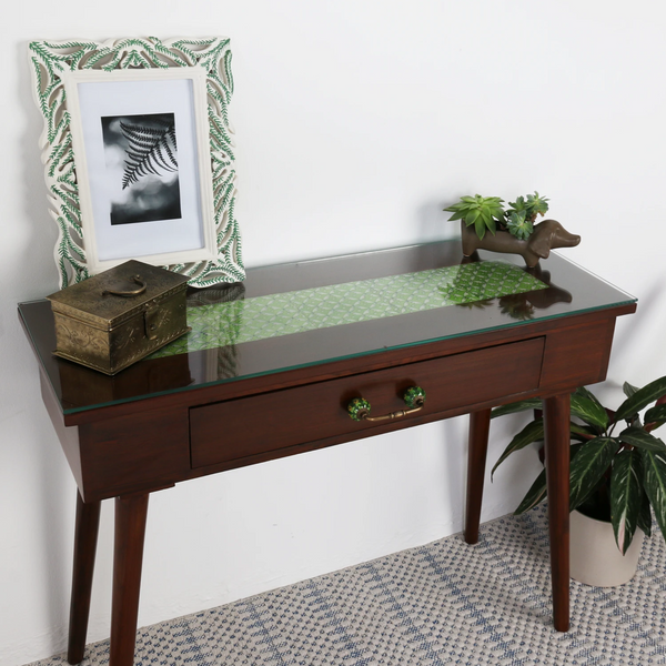 Brown console table with green tile inlay pictured with plants