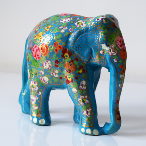 Turquoise paper mache elephant with multicoloured flowers and green leaves on trunk and body- side view