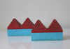 side view of a pair of pyramid boxes- turquoise base and red pyramid top