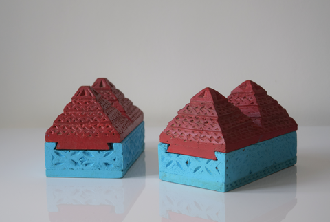 angled view of a pair of pyramid boxes- turquoise base and red pyramid top