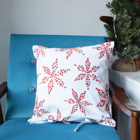 "Poinsettia Embroidered Cushion Cover 16"" x 16"" on Blue Chair"