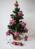 Purple star shaped Christmas decorations with pink, yellow embroidery and mirror work on Christmas tree