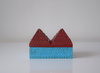 side view of a pyramid box- turquoise base and red pyramid top