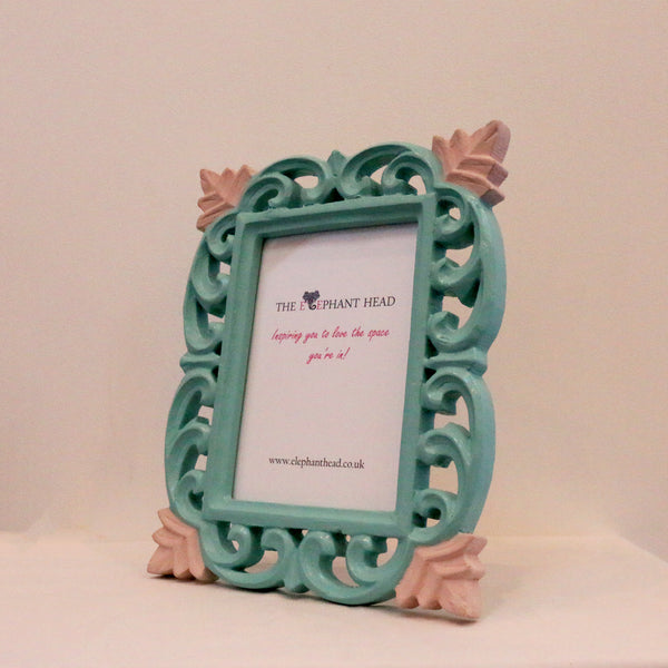 Teal surround and light pink flowers side view of picture frame