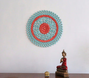 Teal and red carved circular wall art with buddha in the picture